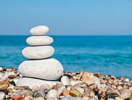 Zen stones stacked at beach against a blue sky and sea with copy space